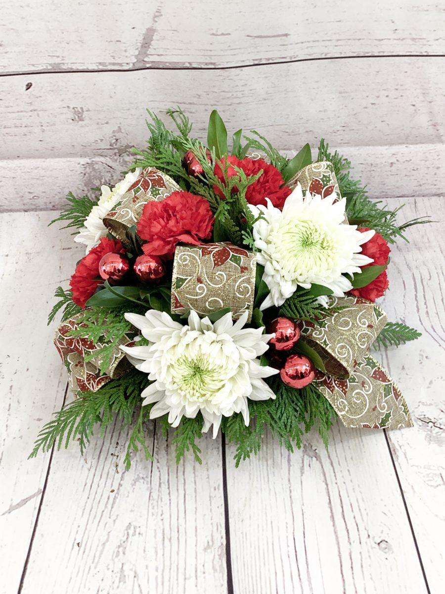 A holiday centrepiece with ribbons, greenery, and mums.